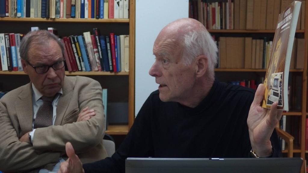Emeritusprofessori Kaarle Nordensteng heiluttelee juuri julkaisemaansa kirjaa. Taka-alalla istuu vakava mies kädet puuskassa.